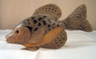 <h5>Stylized Crappie by Joe Anderlik</h5><p>This fish was carved in the early 1980's and is Tan, Grey, Golden Yellow and Black with orange and black eyes. it measures 9 inches long and about 5 inches tall.</p>
